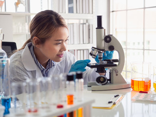 asian scientist working in laboratory with microscope