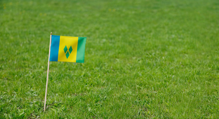 Saint Vincent and the Grenadines flag. Photo of a flag on a green grass lawn background. Close up of national flag waving outdoors.