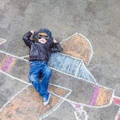 Funny little kid boy flying by a plane picture painting with colorful chalk. Creative leisure for children outdoors in summer