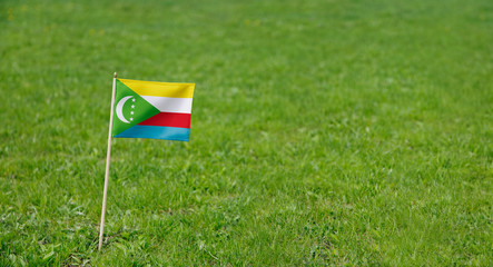 Comoros flag. Photo of  Comoros flag on a green grass lawn background. Close up of national flag waving outdoors.