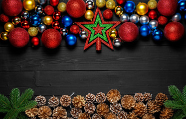 Christmas holiday background. New Year black stylish background and frame with fir branch, pine cones and xmas toy balls. Copy space. Top view