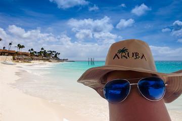 sun glasses and Aruba hat on a leg. Eagle beach on background