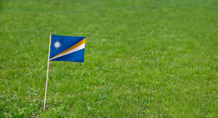 Marshall Islands flag. Photo of Marshall Islands flag on a green grass lawn background. Close up of national flag waving outdoors.