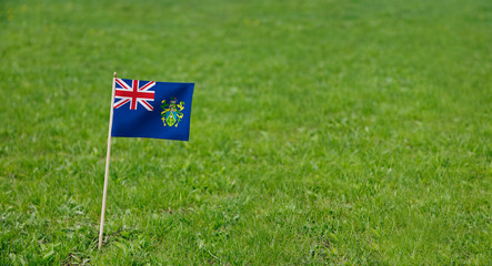 Pitcairn Islands flag. Photo of Pitcairn Islands flag on a green grass lawn background. Close up of national flag waving outdoors.