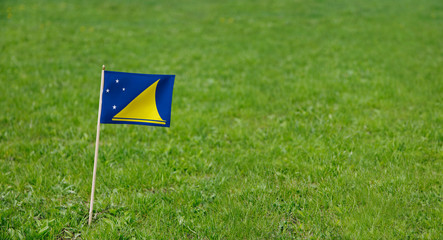 Tokelau flag. Photo of Tokelau flag on a green grass lawn background. Close up of national flag waving outdoors.