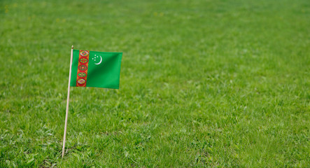 Turkmenistan flag. Photo of Turkmenistan flag on a green grass lawn background. Close up of national flag waving outdoors.