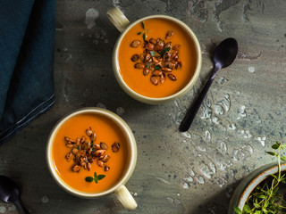 Overhead view of pumpkin soup served in mugs