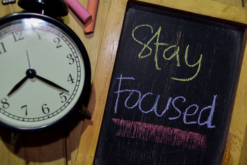 Stay Focused on phrase colorful handwritten on chalkboard and alarm clock with motivation, inspiration and education concepts. Table background
