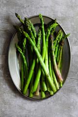Raw asparagus spears on a plate.