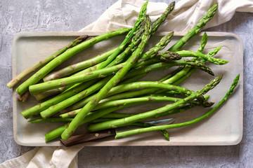 Freshly cut asparagus on a wooden tray.