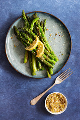 Chargrilled asparagus on a plate with a fork and bowl of pistachio dukkah.