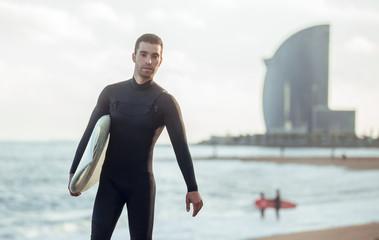 Cheerful man with surfboard on beach