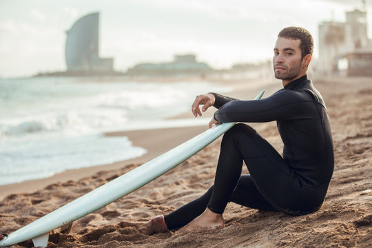 Portrait of young man with surfboard sitting on sand