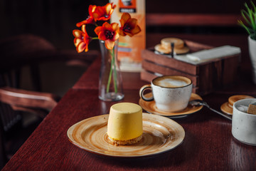 Dessert with mango and a cup of cappuccino in a cafe with a retro interior