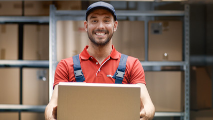Portrait of Handsome Warehouse Worker in Uniform Gives Cardboard Box Package and Smiles.