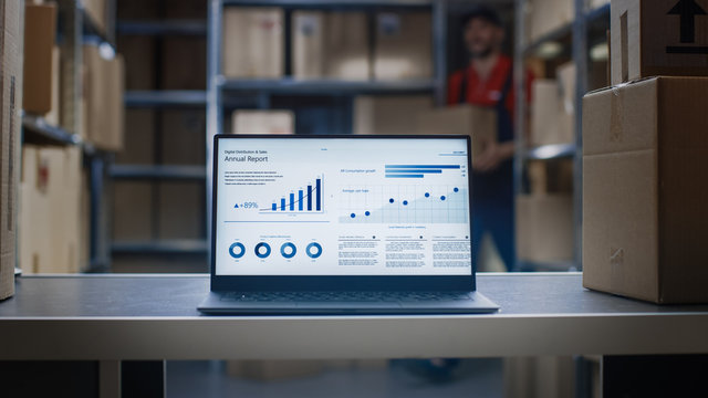 Laptop Screen with Infographics Displaying Graph and Statistics with Annual Results Growth Standing in Warehouse.