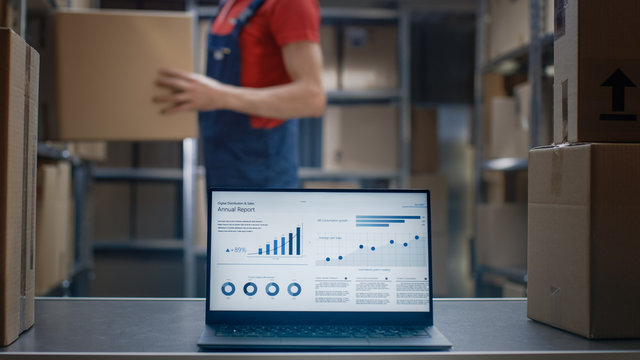 Laptop Screen with Infographics Displaying Graph and Statistics with Annual Results Growth Standing on the Desktop in the Warehouse where Man Works.