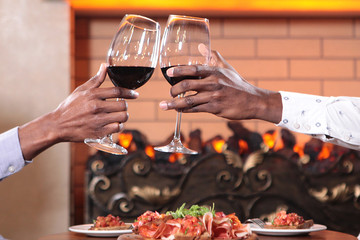 African American hands on glasses of red wine raised for toast . Macro photo in the interior. The concept of rest and communication.
