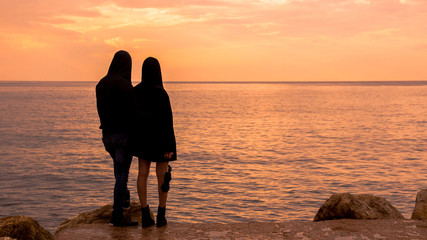 a couple looks at the sea at sunset
