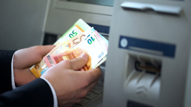 Man counting euros withdrawn from ATM, 24h service, easy banking operation