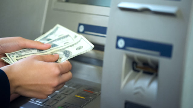 Woman counting dollars withdrawn from ATM, 24h service, easy banking operation