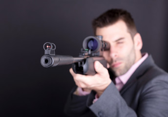 Man in suit with rifle and scope