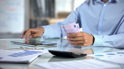 Businessman counting euro and planning company budget by tablet application
