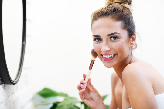 Young woman applying makeup with brush in bathroom