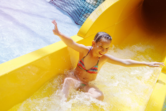 Young pretty girl in a striped colorful swimsuit laughs, rides on a yellow water slide in aqua park.