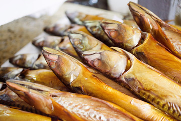 Smoked mackerel on counters in the market. Sea fish