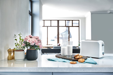 Cookies and Milk with an glass milk bottle on a kitchen counter for a after school snack of cookies and milk