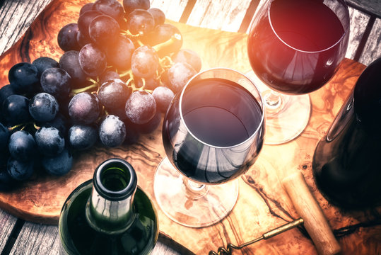 Setting with bottles of red wine and glasses