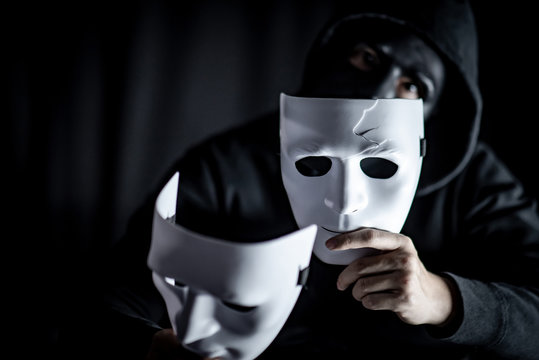Mystery hoody man wearing black mask holding two white masks in his hand. Anonymous social masking. Major depressive disorder or bipolar disorder. Halloween concept