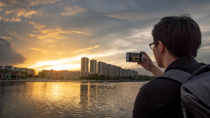 Asian man with glasses using smartphone camera taking photo during the sunset in the city. Urban lifestyle with mobile phone technology concept