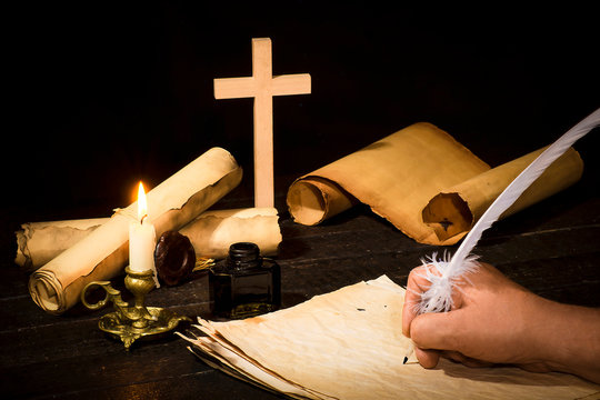 A hand writing with a pen on the background of papyrus scrolls, against the background of a candle and a cross