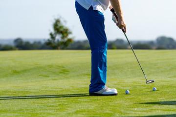 Golfer spielt Golf auf einem Golfplatz mit Driver und Golfball.