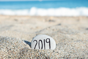 2019, as the new year, in a stone on the beach