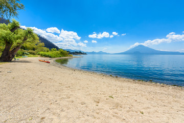 Paradise beach with chair and kayak at lake Atitlan, Panajachel - Relaxing and recreation at beach with vulcano landscape scenery in the highlands of Guatemala