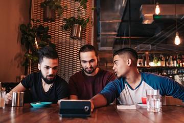 Group of arabian friends taking selfie in lounge bar. Mixed race young men having fun