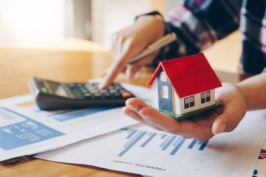 Woman holding house model in hand and calculating financial chart for investment to buying property.