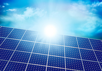 Solar photovoltaic panel with sun reflection. Background with sky and clouds