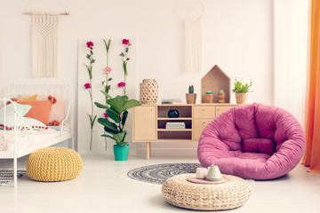 Stylish teenage girl bedroom with comfortable bed, macrame on the wall, flower board, wooden cabinet and pink pouf