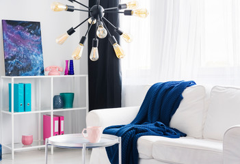 Blue blanket on white couch and silver table under lamp in bright flat interior with poster. Real photo