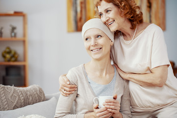 Two positive woman sitting together at home enjoining their time after radiation therapy