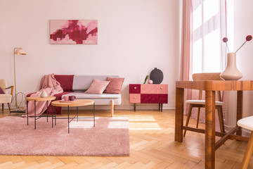 Flowers on wooden table in pink apartment interior with sofa under poster next to cabinet. Real photo