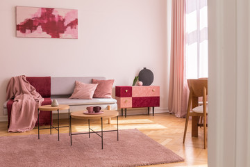 Poster above grey sofa with pillows in bright living room interior with table on pink carpet. Real photo