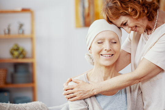 Senior redhead woman hugging her friend who is suffering from leukemia
