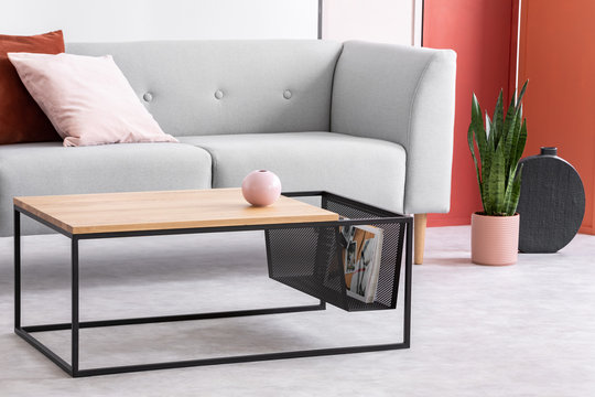 Closeup of modern wooden and metal coffee table next to stylish grey couch in trendy living room