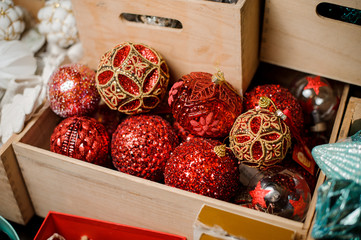 Box of many glittering red toy bulbs of different shapes