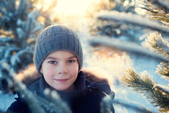 Portrait of a boy in the winter forest in the evening.